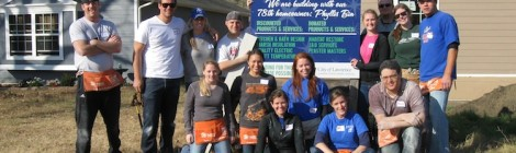 The whole crew from the Thomas More Society poses by the Habitat for Humanity sign at the end of the day.